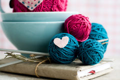 Bright balls of yarn in blue plates and heart made ​​of felt