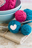Bright balls of yarn in blue plates and heart made of felt Stock Photography