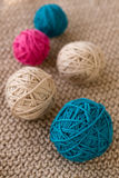 Bright balls of yarn lying on knitted plaid Stock Photo