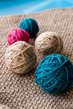 Bright balls of yarn lying on knitted plaid Royalty Free Stock Photo