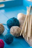 Bright balls of yarn, wooden knitting needles, knitted blanket Royalty Free Stock Photo