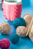 Bright balls of yarn, wooden knitting needles, knitted blanket Royalty Free Stock Photos