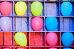 Bright baloons in cells at balloon darts. Close up amusement park attraction of bright colorful ballons in cells for bursting with darts Stock Image