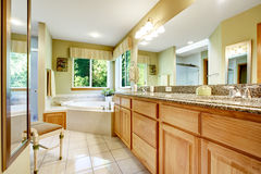 Bright bathroom with corner bath tub. Cabinet with granite top and large mirror Stock Photo
