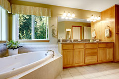 Bright bathroom with corner bath tub. Cabinet with granite top and large mirror Stock Images