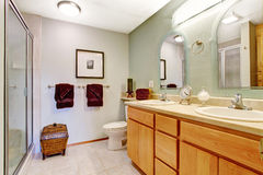 Bright bathroom interior with honey vanity cabinet Royalty Free Stock Photo