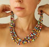 Bright beads of Murano glass on a young girl. A girl dresses and button beads, jewelry.  stock photography