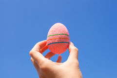 Bright Beautiful Easter egg in hand on background Stock Photo