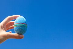 Bright Beautiful Easter egg in hand on background Royalty Free Stock Image