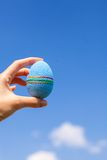 Bright Beautiful Easter egg in hand on background Stock Photography