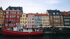 Bright beautiful facades of the buildings on the waterfront Nyhavn and the red-white ship on the water. Denmark Stock Photo