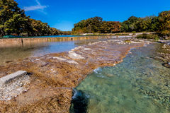 Bright Beautiful Fall Foliage on the Crystal Clear Frio River. Royalty Free Stock Photo