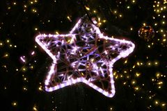 Bright beautiful glowing star on a Christmas tree in the evening. Bright beautiful glowing star close-up on a Christmas tree in the evening stock images
