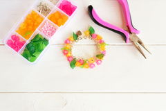 Bright beautiful hand bracelet with pink and yellow acrylic beads flowers and green leaves. Pliers Royalty Free Stock Image