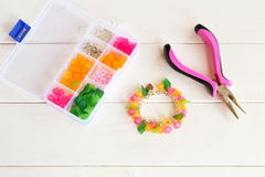 Bright beautiful handmade bracelet. Pliers. Organizer with beads, plastic flowers and accessories for handmade jewelry Stock Image