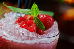Bright beautiful and tasty alcoholic cocktail or lemonade with a cap of frozen ice, mint and fresh raspberries on the bar with a n. Bright beautiful and tasty Royalty Free Stock Photo