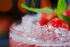 Bright beautiful and tasty alcoholic cocktail or lemonade with a cap of frozen ice, mint and fresh raspberries on the bar with a n. Bright beautiful and tasty Stock Photography