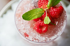 Bright beautiful and tasty alcoholic cocktail or lemonade with a cap of frozen ice, mint and fresh raspberries on the bar with a n. Bright beautiful and tasty Royalty Free Stock Photography