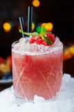 Bright beautiful and tasty alcoholic cocktail or lemonade with a cap of frozen ice, mint and fresh raspberries on the bar with a n. Bright beautiful and tasty Stock Images