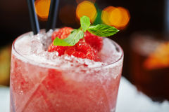Bright beautiful and tasty alcoholic cocktail or lemonade with a cap of frozen ice, mint and fresh raspberries on the bar with a n. Bright beautiful and tasty Stock Photos