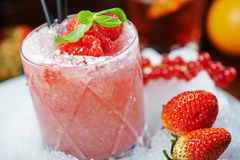 Bright beautiful and tasty alcoholic cocktail or lemonade with a cap of frozen ice, mint and fresh raspberries on the bar with a n. Bright beautiful and tasty Royalty Free Stock Photos