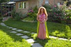 Bright beautiful woman standing near village house around flower Stock Photo