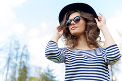 Bright beautiful young happy girl in hat and sunglasses walking in the park on a sunny day Stock Image