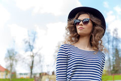 Bright beautiful young happy girl in hat and sunglasses walking in the park on a sunny day Royalty Free Stock Photos