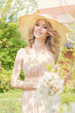 Bright beautiful young happy woman walks through the park near a flowering tree on a sunny day in summer hat and a sundress Stock Photos