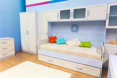 Bright bedroom with a bed and cupboard Stock Photos