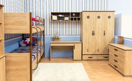 Bright bedroom with a bed cupboard and table Royalty Free Stock Image