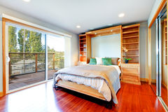 Bright bedroom with storage combination, hardwood floor and glas Stock Image