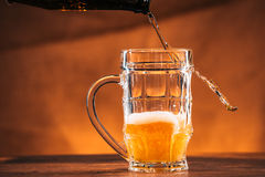 Bright beer is poured into a glass mug Royalty Free Stock Images