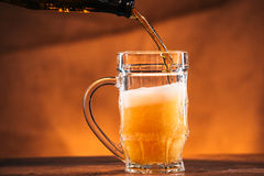 Bright beer is poured into a glass mug Stock Photo