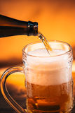 Bright beer is poured into a glass mug Royalty Free Stock Photography