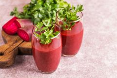 Bright beetroot smoothie in tumbler with fresh pieces of beet. And parsley on cutting board. Gray slate background. Horizontal view. Copy space stock image