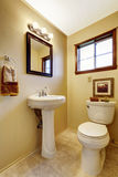 Bright beige bathroom interior with old washbasin stand, toilet and tile floor. Stock Photography