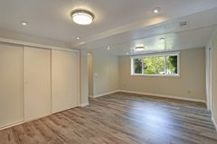 Bright beige large empty room with hardwood floor stock photography