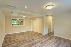 Bright beige large empty room with hardwood floor. Built-in closet, small window. American house interior design Stock Images
