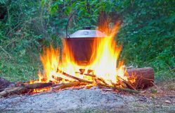 Bright big fire under the pot with food in the forest. Cooking over an open bonfire in a hike; campfire background, camping, evening, adventure stock images