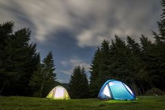 Bright big moon in dark blue cloudy sky over two tourist tents on green grassy forest clearing among tall pine trees on distant. Mountain background. Tourism stock photo