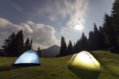 Bright big moon in dark blue cloudy sky over two tourist tents on green grassy forest clearing among tall pine trees on distant. Mountain background. Tourism royalty free stock photography