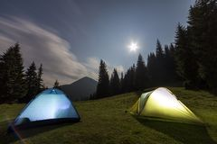 Bright big moon in dark blue cloudy sky over two tourist tents on green grassy forest clearing among tall pine trees on distant. Mountain background. Tourism royalty free stock photo