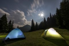 Bright big moon in dark blue cloudy sky over two tourist tents on green grassy forest clearing among tall pine trees on distant. Mountain background. Tourism stock photography