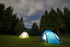 Bright big moon in dark blue cloudy sky over two tourist tents on green grassy forest clearing among tall pine trees on distant. Mountain background. Tourism stock images