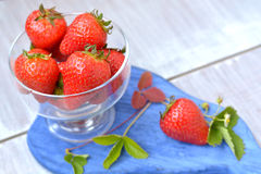 Bright, big strawberry in glass dish on foreground. Bright, big, homegrown strawberry in glass dish on foreground close up - summer harvest Stock Photography