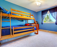 Bright blue bedroom with bulk bed. Bright blue bedroom for kids with wooden bulk bed and nightstand royalty free stock photography