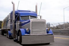 Bright blue big rig semi truck with flat bed trailer transportin. Face of blue American classic popular powerful big rig semi truck tractor with huge grille and Stock Images
