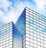 Bright Blue City Building Construction. Bright blue city buildings with the sky clouds reflecting on them. The bottom is a blueprint layout sketch fading to a
