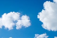 Bright blue cloudy sky. Puffy white clouds on a summer day stock photos